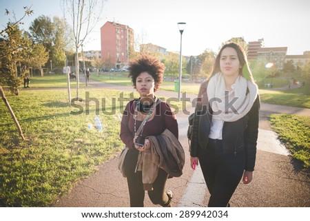 two multiethnic beautiful young woman black and caucasian having fun in town #289942034