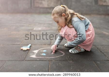little girl draws a chalk on asphalt