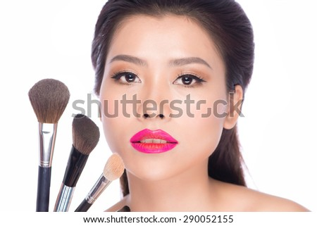 Beauty Asian Girl with Makeup Brushes. Natural Make-up for Brunette Woman with Brown Eyes. Beautiful Face. Makeover. Perfect Skin. Applying Makeup #290052155