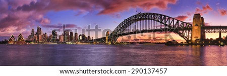 burning bright sunset over Sydney CBD cityline pictured panoramic across Harbour including skyscrapers and harbour bridge Royalty-Free Stock Photo #290137457