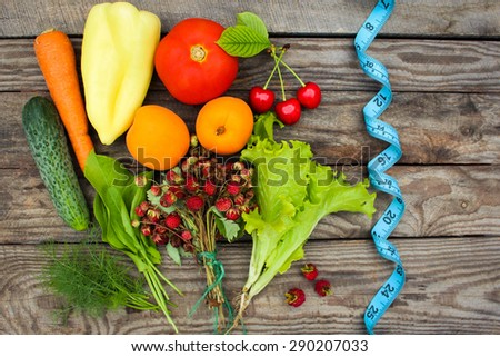 Fruits, vegetables and in measure tape in diet on wooden background #290207033