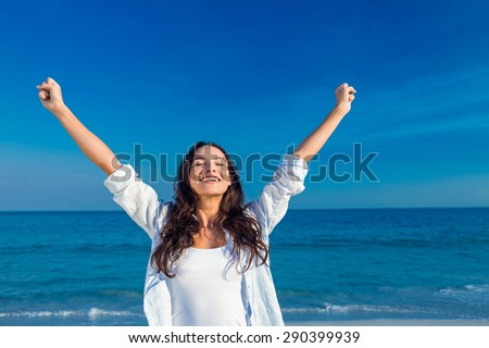 Happy woman smiling at the beach on a sunny day Royalty-Free Stock Photo #290399939