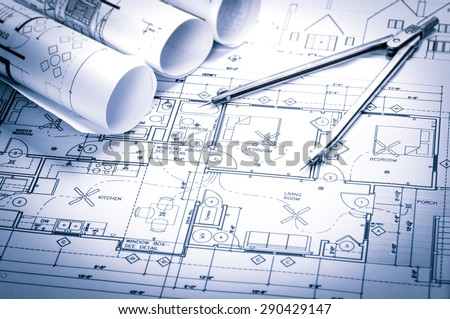 rolls of architecture blueprints and house plans on the table and drawing compass Royalty-Free Stock Photo #290429147