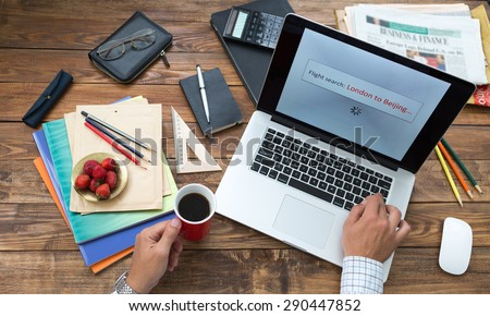 Booking flight tickets on-line concept. Man working on computer booking air flight tickets screen searching best offer from London to Beijing wooden desk stationery books pen pencil color on table #290447852