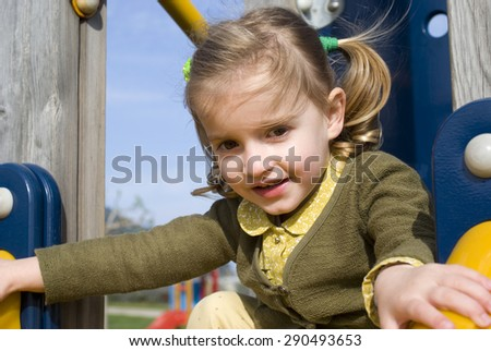 Young girl on slide in playground #290493653