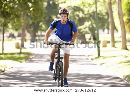 Man Cycling Through Park #290612612