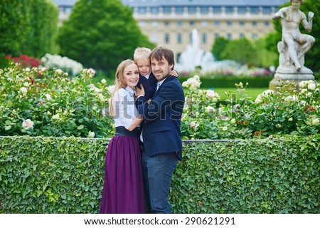 Happy family of three in the beautiful garden of Palais Royal in Paris