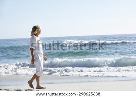 Senior Woman Walking along Sandy Beach #290625638