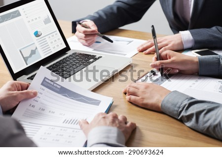Business professionals working together at office desk, hands close up pointing out financial data on a report, teamwork concept #290693624