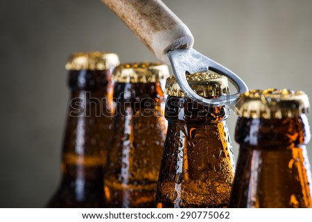 Brown ice cold beer bottles with water drops and old opener Royalty-Free Stock Photo #290775062