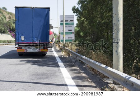 Trucks waiting a customs clearance or to pay on a toll plaza, outdoor horizontal shot