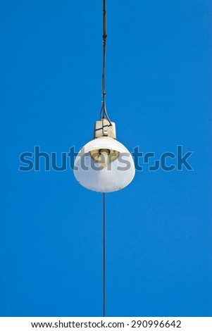 Single streetlight hanging from a metal cable on a blue background.