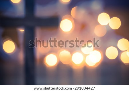 Wooden Christian Cross out of focus with a soft bokeh lights background
