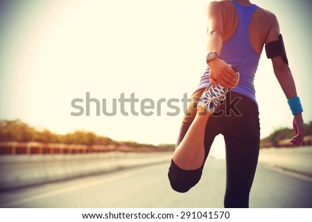 Young fitness woman runner stretching legs before run on city Royalty-Free Stock Photo #291041570