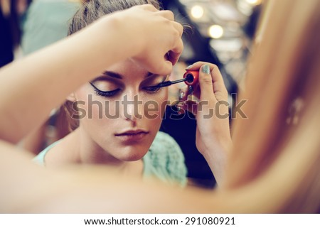 Make-up artist applying the mascara to model. Close up.  Royalty-Free Stock Photo #291080921