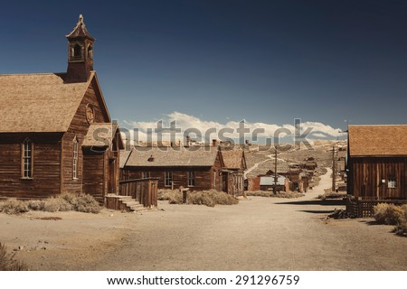 Colored vintage old looking photo of empty streets of abandoned ghost town Bodie in California, USA in the middle of a day. Royalty-Free Stock Photo #291296759