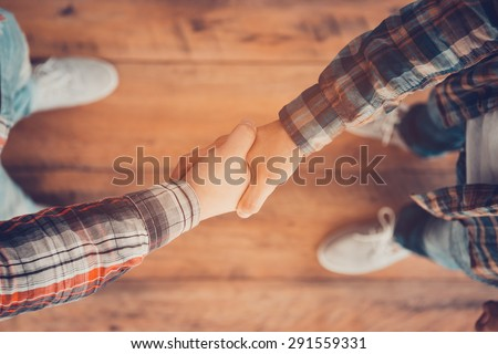Men shaking hands. Top view of two men shaking hands while standing on the wooden floor #291559331