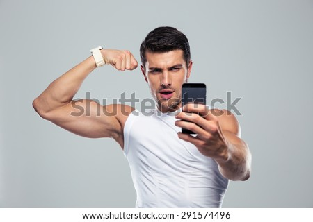 Sports man making selfie photo on smartphone over gray background