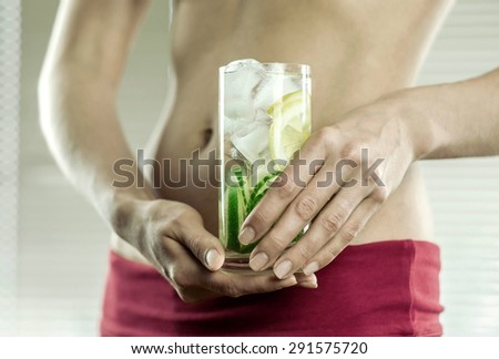Healthy coctail in the hands of fitness female. #291575720