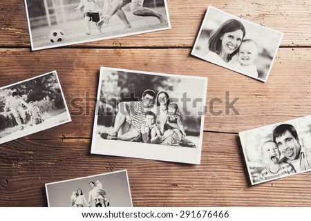 Black and white family photos laid on wooden table background.