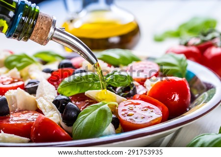 Caprese Italian or Mediterranean salad. Tomato mozzarella basil leaves black olives and olive oil on wooden table. Royalty-Free Stock Photo #291753935