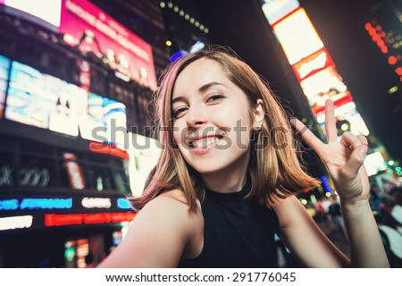 Young woman tourist laughing and taking selfie photo in New York City, Manhattan, Times Square. Female traveler and photographer takes picture for her blog.