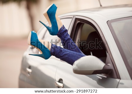 Beautiful woman legs with shoes in car window on vacation. Girl's legs in high heel shoes. Concept of happiness and fun during the trip in summer, Instagram style filters, selective focus. series #291897272