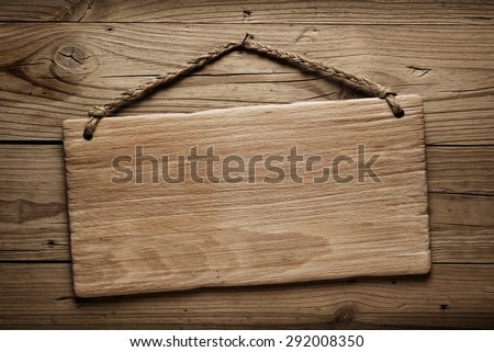 wooden signboard hanging on a western saloon wall