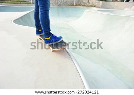Skateboarder legs riding skateboard at skatepark #292024121