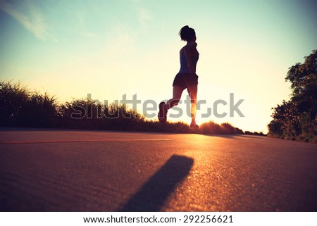 young fitness woman running on sunrise seaside trail #292256621