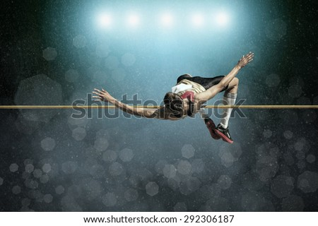 Athlete in action of high jump. Royalty-Free Stock Photo #292306187