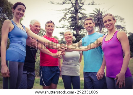 Happy athletic group putting their hands together on a sunny day #292331006