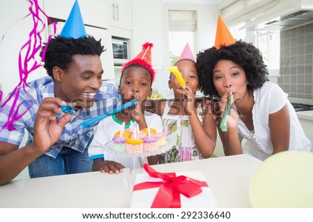 Happy family celebrating a birthday together at home in the kitchen #292336640