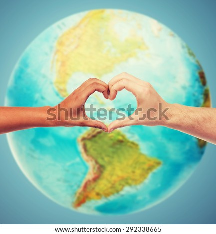 people, peace, love, life and environmental concept - close up of human hands showing heart shape gesture over earth globe and blue background Royalty-Free Stock Photo #292338665
