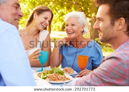 A senior and a young adult couple eating together outdoors #292701773