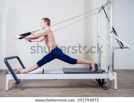 Pilates reformer workout exercises man at gym indoor #292794872