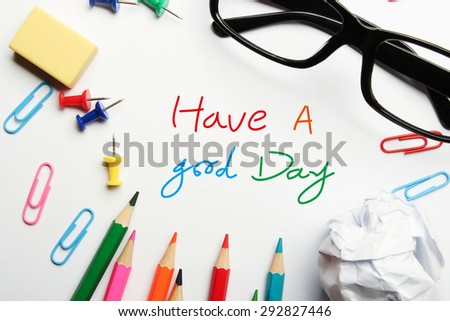 Have a good day concept with some office supplies around it on white background.