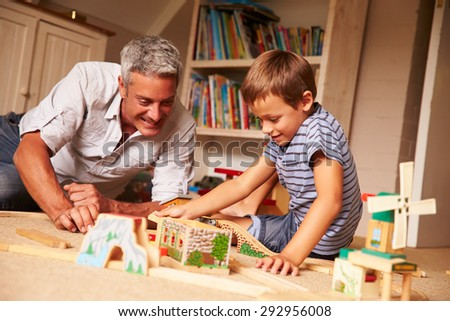 Father playing with son and toys on the floor in a playroom #292956008