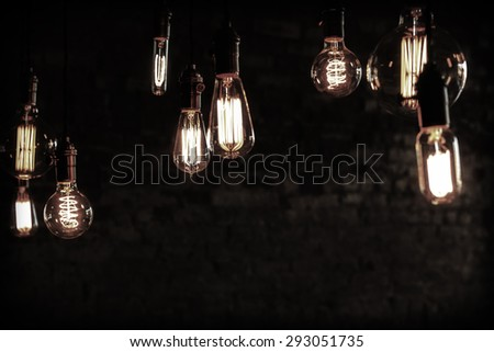 Decorative antique edison style filament light bulbs against brick wall #293051735