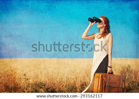 Redhead girl with suitcase and binocular at countryside road near wheat field. Photo in old color image style.