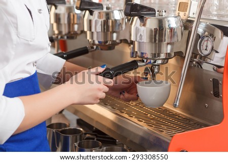 In process. Close-up portrait of young female barista making coffee by using special machine. #293308550