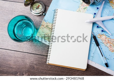 travel , trip vacation, tourism  mockup - close up of compass, glass of water note pad, pen and toy airplane and touristic map on wooden table. Empty space you can place your text or information. #293481968