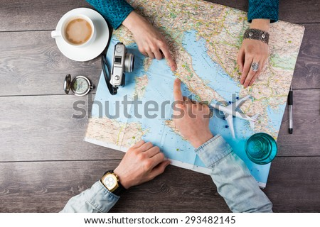 Young couple planning honeymoon vacation trip with map. Top view. Pointing to Europe Rome Royalty-Free Stock Photo #293482145
