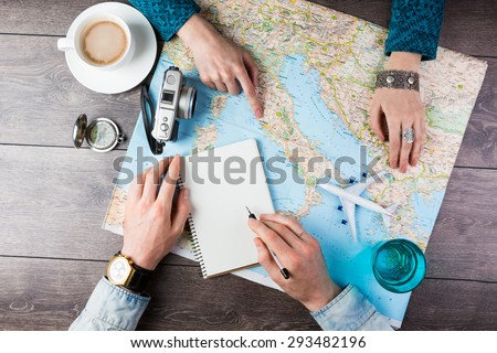 Two young people together planning trip to Europe. Top view. empty white space in notebook where you can place your text or advertisement.  Romantic travel Royalty-Free Stock Photo #293482196