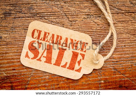 clearance sale sign a paper price tag against rustic red painted barn wood #293557172