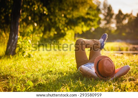 Trendy Hipster Girl Relaxing on the Grass Royalty-Free Stock Photo #293580959