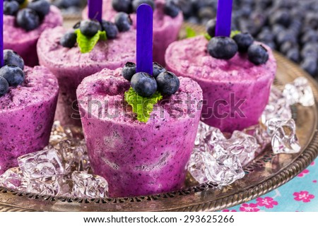 Homemade blueberry popsicles made in plastic cups. #293625266