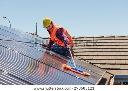 Young worker cleaning solar panels on the roof.Focus on the worker. #293683121
