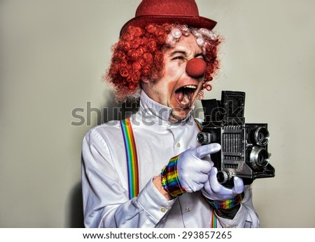 Clown photographer wearing a red hat and wig with a vintage camera on a white background