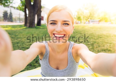POrtrait of a smiling young girl making selfie photo in park